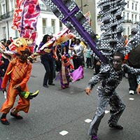 Members of elimu dressed in the orange creature and the robot inspired costume perfoming together.