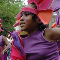 Woman dressed in purple with orange details, a brown belt, a pink headdress and a flag in her hand.