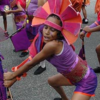 Members of Elimu performing a dance cheography during the carnival. The members wear purpe outfits with orange details, a brown belt and a pink headdress.