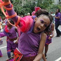 Member of Elimu, dressed in purple and orange, jumping during the carnival parade.