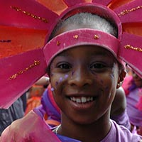 Smiling youngster with a pink and orange headdress.