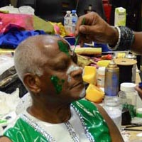 Man gets his face painted in green and white.
