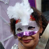 Woman wearing a mask out of sparkling stones, with a purple space below and a white feather on the top.