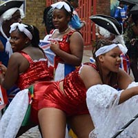 Women wearing red with white lace parts and holding union jack flags, dancing together.