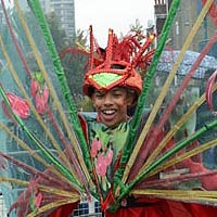 Member of Elimu dressed in red, with a red headdress and a wings inspired transparent green construction with red chillis on it.
