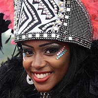 Close-up of a woman with pink and turquoise sparkling small stones beneath her eyes and a crown in front of her pink feather headdress. The crown is black with a white design and sparkling little stones on it.