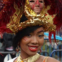 Close-up of a woman wearing a big golden necklace and a big golden and red headdress with a red sparkling mask on it.