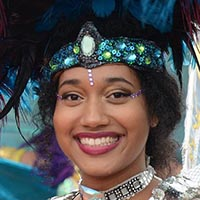 Close-up of a woman with small stones between her eyes, a crown out of various sparkling blue and green stones and black and blue feathers above it.