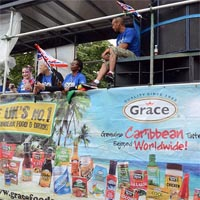 """Members of Elimu wearing blue Elimu-Shirts and holding union jack flags, standing or sitting on a truck, with a banner of """"Gracefoods"""" on its side."""