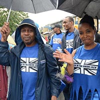 Two members of Elimu in blue Elimu Shirts with an Union Jack Logo on it, holding black umbrellas.