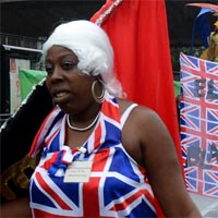 Sophie wearing a Union Jack dress and white wig carring a flag at the parade with a big banner and a lion as background