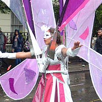 Woman dressed in white with purple and pink parts, a white mask and a huge butterfly wing inspired construction out of various purple fabrics.