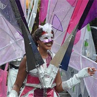 Woman dressed in white with purple and pink parts, a silver sparkling and purple mask and a huge butterfly wing inspired construction out of various purple fabrics.