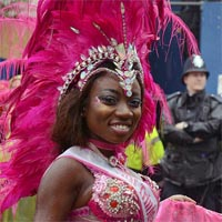 Female member of Elimu dressed in a pink and silver sparkling bra and holding a pink cloth. In the background policemen are standing, marking the line between the audience and the parade.