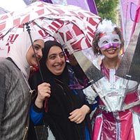 Member of Elimu dressed in white with purple parts, wearing a white and purple mask and a butterfly wing inspired construction out of various purple fabris on her back taking a picture with visitors of the Notting Hill Carnival.