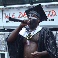 Man wearing a white underwear with a colourful stripe in the middle, a black sparkling coat and a hat. He is blowing in a black horn celebrating the Notting Hill Carnival.