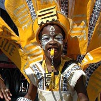 Photograph of boy carnival dancer in yellow costume, whistle in mouth, a backpack supports large yellow wings and a tribal mask above him.