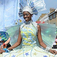 Photograph of carnival dancer in white and yellow costume with a wide skirt and a blue and white headdress.