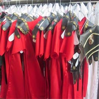 Photograph of red roman costumes with golden and black leather elements, on a clothes rail.