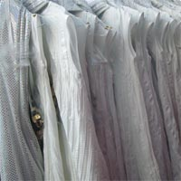 Photograph of white costumes on a clothes rail.