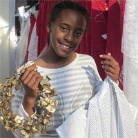 Girl holding a golden wreath and a white costume.