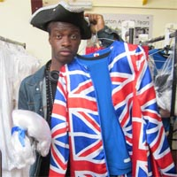 Man holding a costume with the union jack pattern on it and a white wig.