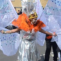 Photo of a woman wearing a swan costume, with a silver dress and a backpack supporting white wings.