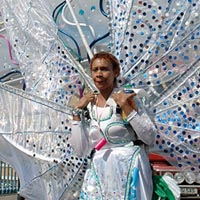 Photo of a woman in a white costume, with a backpack supporting translucent wings.