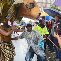 Photo of man wearing brown costume and gold mask carrying above on a backpack a huge lion head with golden mane. In the foreground a steward waits while people in the crowd take pictures.