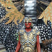 Nolan wearing a gold and silver decorated armour-like breastplate, with shoulder pieces and helmet. Towering above and behind him are huge black and gold wings.