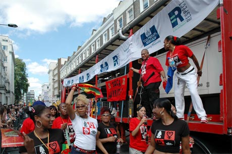 Photo showing people wearing carnival T-shirts gathered around the carnival sound truck.