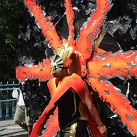 Photo of a male dancer in black and gold costume, on his back a very large circular black construction decorated with spokes of orange flame.