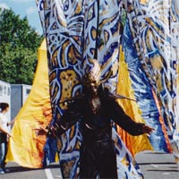 Old photo of Nolan at the parade wearing black costume with golden headdress and big backpack with tribal pattern