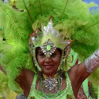 Dancer with costume made of green feathers and materials and elaborate head dress