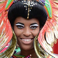 Girl wearing multi-coloured feathered and beaded costume and with black and white eye makup