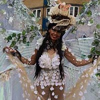Woman at Notting Hill Carnival wearing costume with huge translucent butterfly wings