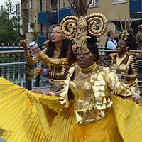 Dancer with ornate golden headdress and pleated gold costume