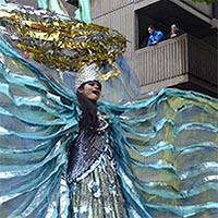 dancer with free flowing translucent costume and small boat as head dress on 10 feet high stilts