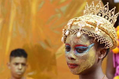 Close-up photo of the face of a girl at Notting Hill Carnival, she is made up with a yellow face, blue and red colour around her eyes, gold glitter applied on top and is wearing a gold headdress topped with a crown.
