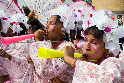 Photo of girls at Notting Hill Carnival. They are wearing pink and white costumes and headdresses and are blowing on coloured plastic vuvuzela horns