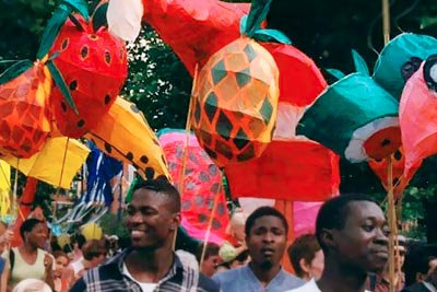 Parade at Notting Hill Carnival showing coloured paper lanterns supported on sticks above the crowd.
