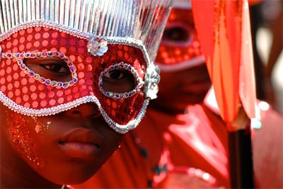 Close-up phot of the face of a girl at Notting Hill Carnival, she is wearing a red sequinned mask edged with silver trim