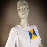 "Photo of Elimu T-Shirt on a mannequin. The T-Shirt is white with a blue and yellow kite and has a ""Zwill in Yuh Tail"" logo on the front."