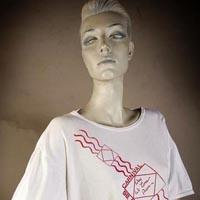 "Photo of Elimu T-shirt on a mannequin. The T-shirt is white and has a red, diagonal and curved design entitled ""Wey We Come From"" on the front."