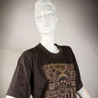 "Photo of Elimu T-shirt on a mannequin. The T-shirt is brown and has a light brown rectangular design entitled ""Columbus Culpa"" on the front."