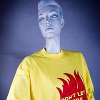 "Photo of Elimu T-shirt on a mannequin. The T-shirt is yellow and has a red flame and a ""Don't let a fire be your fault"" logo on the front."