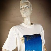 "Photo of Elimu T-Shirt on a mannequin. The T-Shirt is white and has a blue ""Warpspeed the Millenium"" logo on the front."