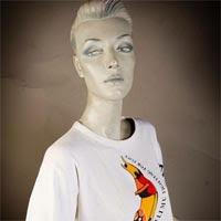 "Photo of Elimu T-shirt on a mannequin. The T-shirt is white and has a multi-coloured design with barbed wire and a ""Fightin for peace"" logo on the front."