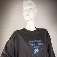"Photo of Elimu T-Shirt on a mannequin. The T-Shirt is black with a blue dancing lady and has a ""Carnival Odyssey"" logo on the front."