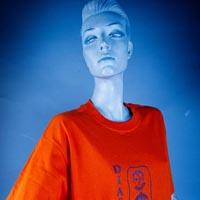 "Photo of Elimu T-shirt on a mannequin. The T-shirt is orange and has a blue design showing three faces in a rectangular form and a ""Diaspora"" logo on the front."